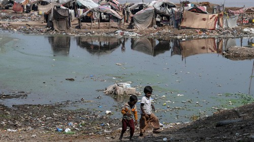 Children walk next to polluted waters in Lahore  (AFP)