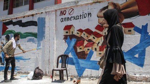 Un murale contro le annessioni dipinto a Rafah (Afp)